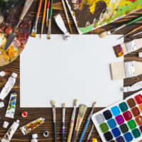 painting-supplies-on-table-around-paper_23-2147895677